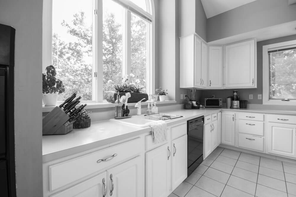 A black and white image of a tidy kitchen with a large window above the sink, looking out to some backyard trees